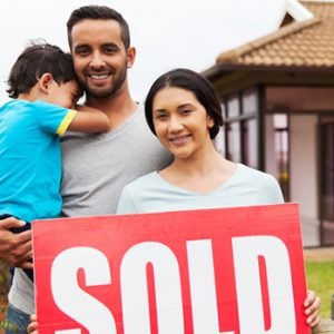 indian family standing outside their house and holding sold sign