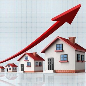 High quality 3d render of miniature houses on a blue graph paper. Housing market concept. Miniature houses are lit by the upper left corner of composition. A red arrow in the composition is symbolizing  a sharp increase in sales. Vertical composition with copy space. Great use for real estate and morgage related concepts.